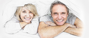 couple smiling and hiding under blanket in bed